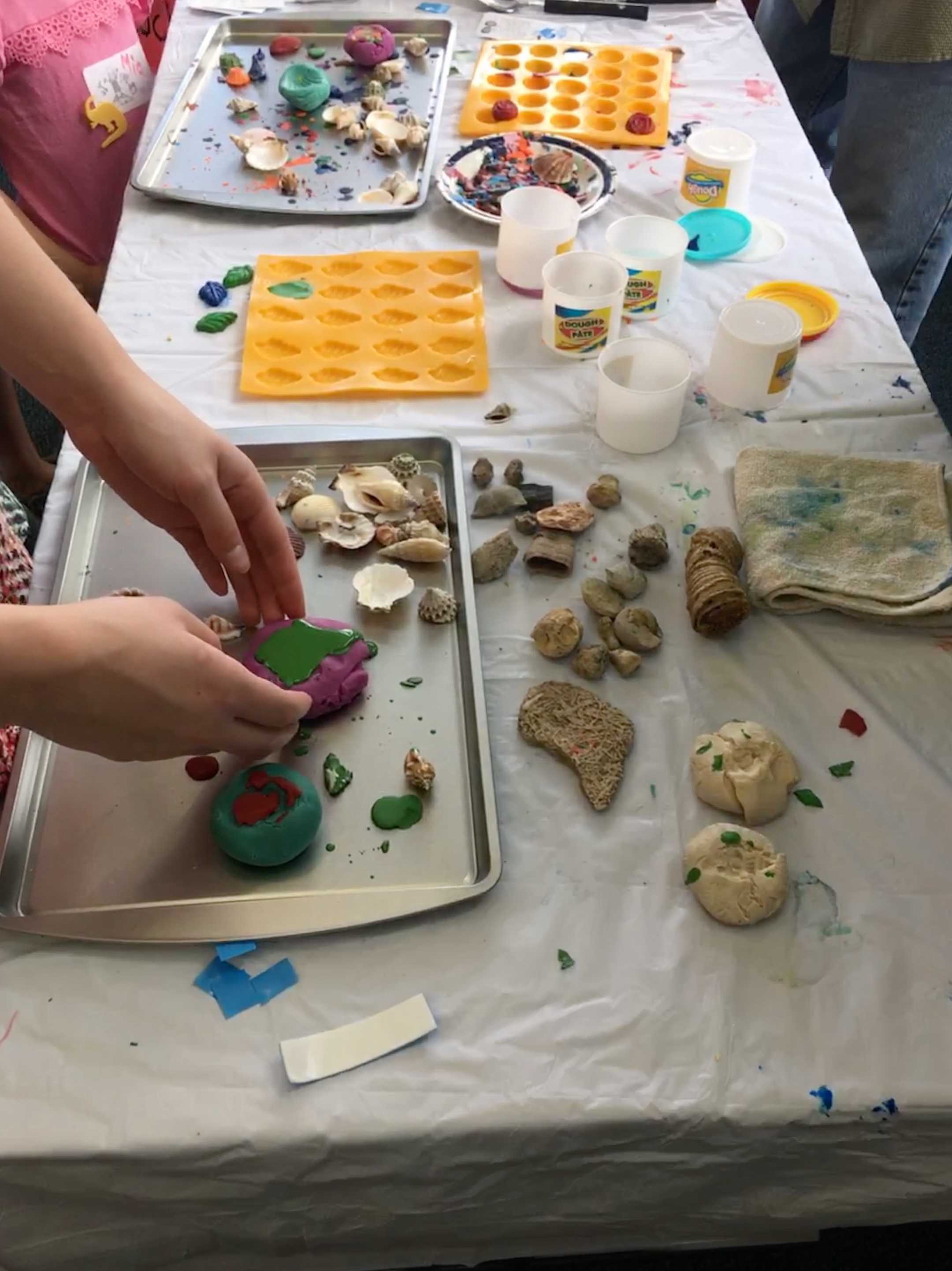 Young attendee sets wax in play-doh mold with the help of Jeffrey Knapp, geography instructor. Photo Credit: Leeanne Ortega